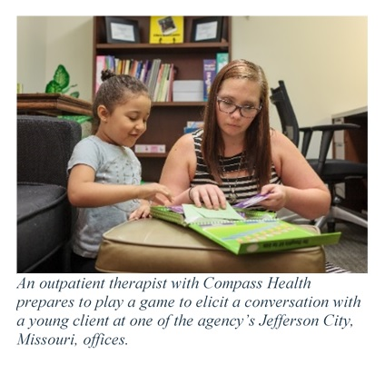 Photo of a Compass Health outpatient therapist with a child. Caption states an outpatient therapist with Compass Health prepares to play a game to elicit a conversation with a young client at one of the agency's Jefferson City, Missouri, offices.