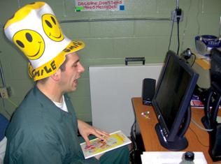 Picture of man with funny hat looking at computer screen.