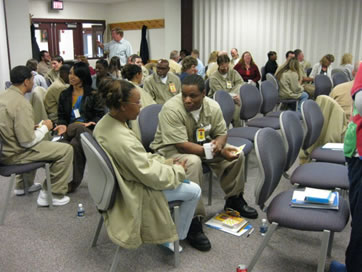 Photograph of a couple's workshop held for incarcerated men and their partners in an Indiana state prison.  The photograph shows individual couples sitting side by side and communicating with one another, with a facilitator at the back of the room.
