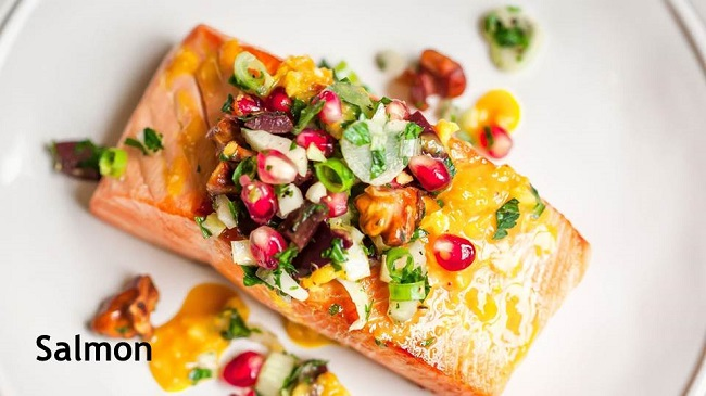 Photo of a plate of salmon with pomegranates and walnuts.