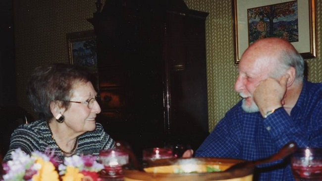 Photo of two older people sitting at a table.