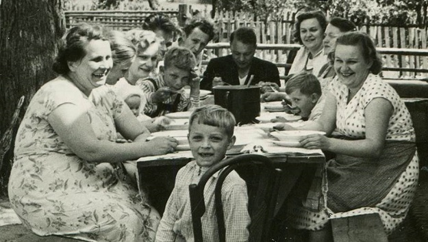 Photo of a large family sitting around a picnic table.